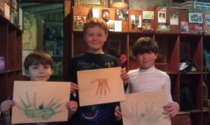 Harrison, Thomas, and Henry showing their examples of our Holiday Hand Art, Menorahs and Reindeer.