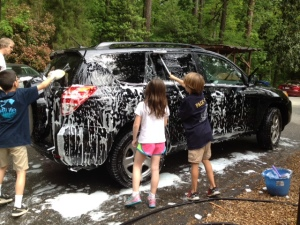Ms. Lisa's Friendship Club third, fourth and fifth graders raise money to support the Defenders of Wildlife by giving arriving parents' cars a good wash and rinse on April 20.